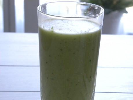 Grön avocado och gurkdrink i glas på vitt bord.