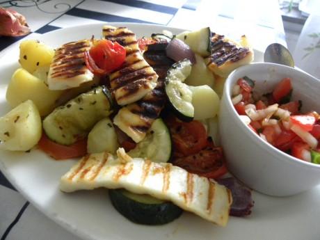 Potatissallad med zucchini, röd lök, tomater dekorerad med halloumi och en skål med tomatsalsa