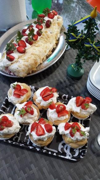 Budapestrulle dekorerad med jordgubbar och marängbakelser med grädde och jordgubbar på utebord vid midsommar