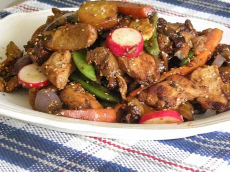 Kyckling med sesamfrön och grönsaker på vitt fat på en blå duk