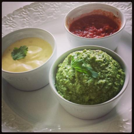En grön pestoröra i vit skål, en tomatsalsa i vit skål, en aioli i vit skål