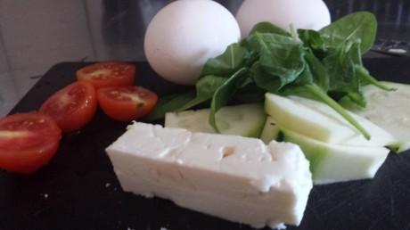 Ingredienser som tomat, fetaost, spenat och ägg till omelett på svart skärbräda