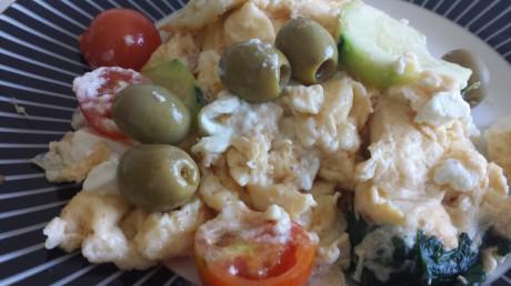 Omelett med tomat, zucchini, spenat, fetaost och oliver på fat som är vitsvart randigt