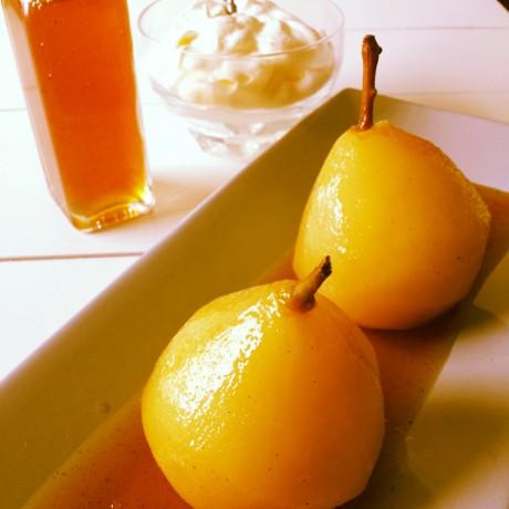 Två päron på ett fat. En flaska med sås och en skål med vispad grädde på ett vitt bord