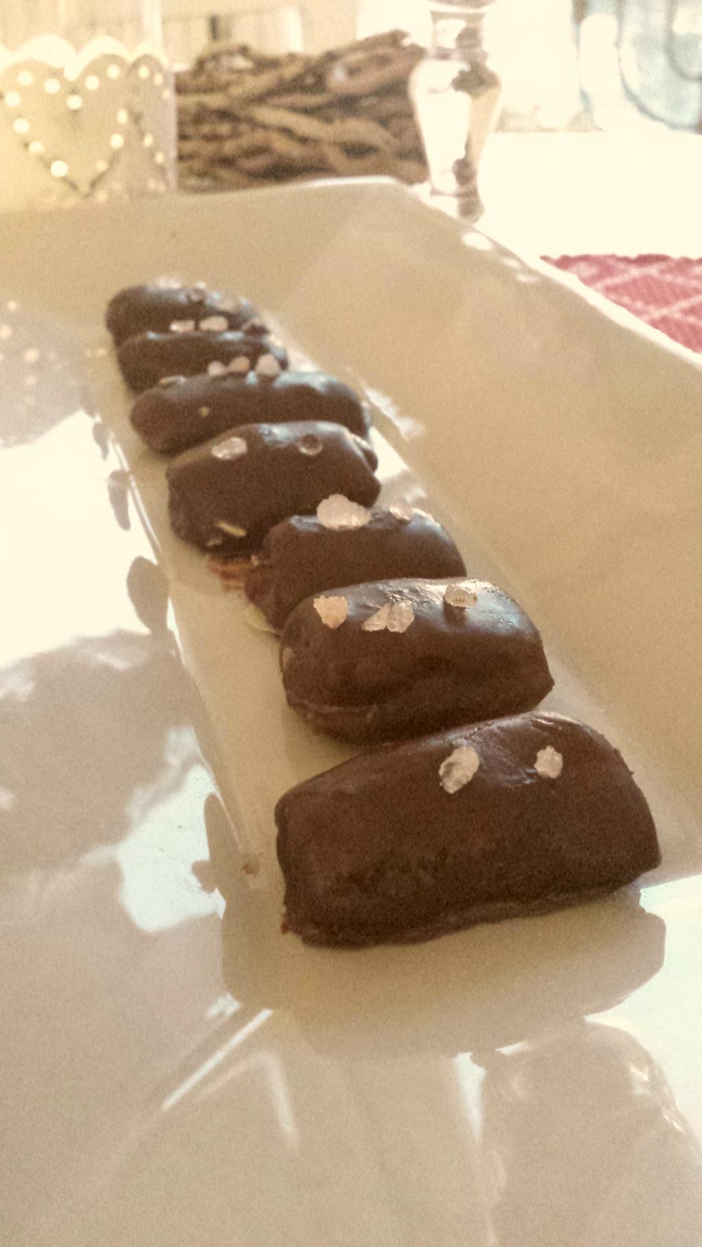 Lakritskola med chokladöverdrag i rad på ett avlångt grått fat