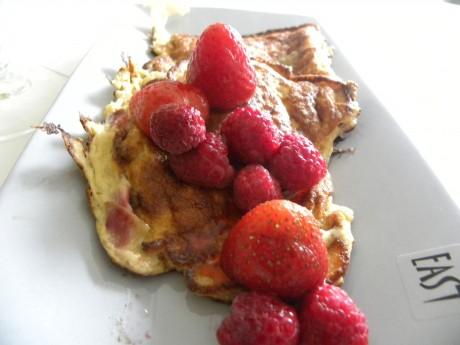 Rabarberpannkaka på grått fat med jordgubbar och hallon.