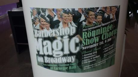 Affisch med Rönninge Show Chorus på en vit pelare
