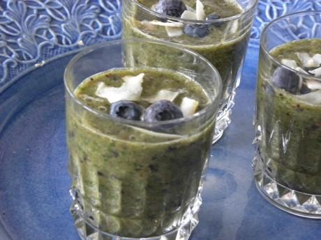 En grön smoothie i glas på ett blått fat, toppade med blåbär och kokosflingor