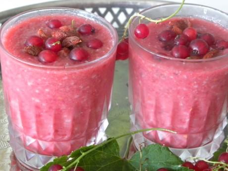 Röda vinbärsmoothie i glas toppade med gojibär och vinbär