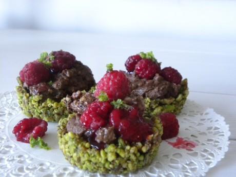 Små gröna spistagebakelser med mintchokladmousse, toppade med hallon