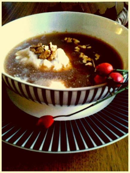 hemmagjord nyponsoppa i ensvartvitrandig skål dekorerad med kokosnötsgrädde och en kvist med nypon