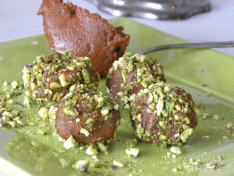 Nyponsmörbollar gjorda på nyponpulver, vatten och kokosolja rullade i pistagenötter på ett grönt fat