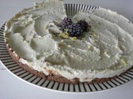 Raw cheesecake dekorerad med citronskal, lavendel och björnbär på ett vitsvartrandigt fat