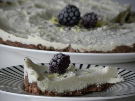 En bit Rawfood cheesecake på ett vitt fat med svarta ränder. I bakgrunden skymtar en hel cheesecake