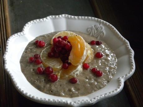 Chiapudding med pepparkakssmak toppad med klyftor av klementin och lingon i en vit djup skål