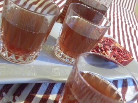 Granatäppleglögg i glas stående på en grå bricka på en rödrandig duk, samt ett halvt granatäpple