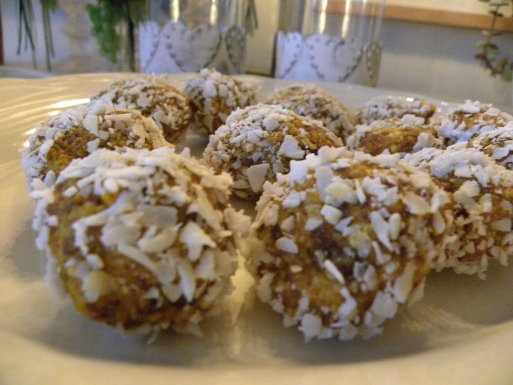 Raw saffransbollar rullade i kokos på ett vitt fat