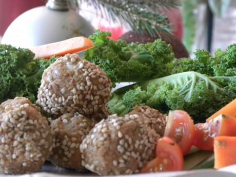 Rawfood solrosfröbollar på ett fat med grönkål och andra grönsaker