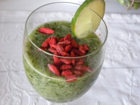 Grön Smoothie i ett glas toppad med gojibär och en limeskiva