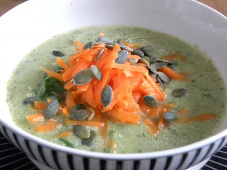 Broccoli och ruccolasoppa i en svart-vitrandig djup skål, toppad med rivna morötter och pumpakärnor