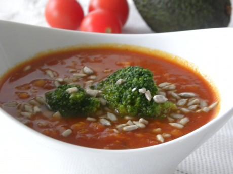 Tomat och linssoppa toppad med broccoli och solrosfrön i en vit djup skål
