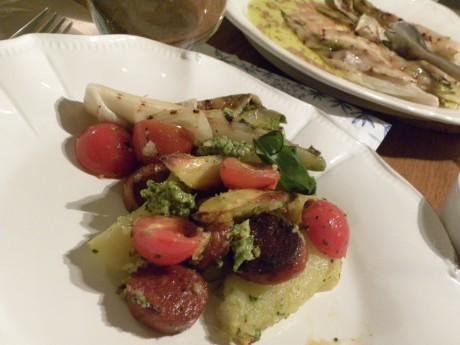 Ugnsrostad potatis och tomater i pestodressing på ett vitt fat