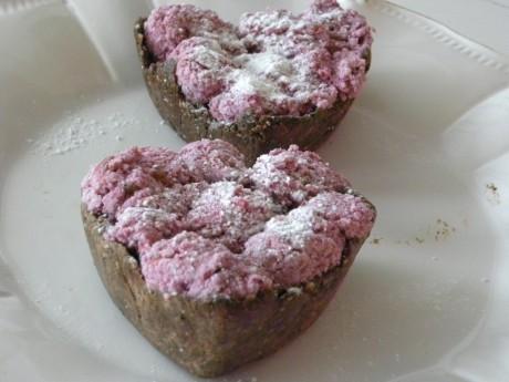 Rawfood Choklad-och lakritsbakelser med hallonmousse på ett vitt fat.