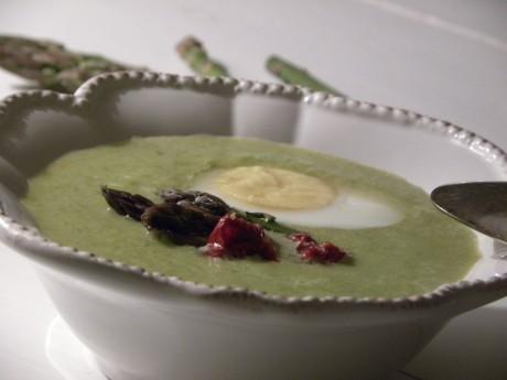 Grön sparris och ärtsoppa toppad med ett ägg i en vit djup tallrik