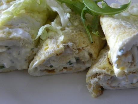 Fyllad omelettrullar på ett vitt fat, toppade med grön sallad