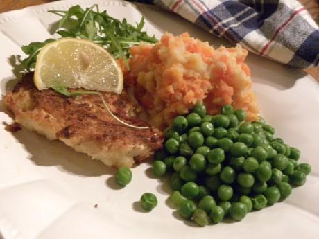 Mandelpanerad torsk med morotsmos och gröna ärter på en vit tallrik