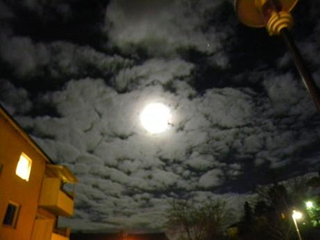 Fullmåne och månsken på en molnig himmel