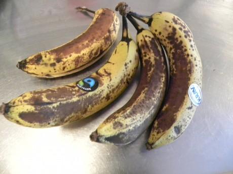 Mogna bruna bananer på ett vitt fat