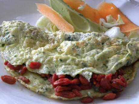Omelett med chia och gojibär samt sallad med avocado och morötter på ett vitt fat