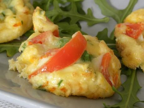 Små omeletter fyllda med ost, tomat och ruccola på en bädd av ruccolasallad på ett grått fat