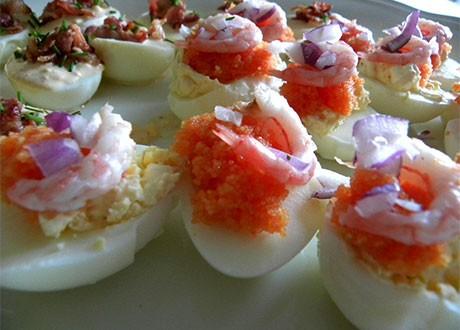 Ägghalvor med rom och räkor på ett fat