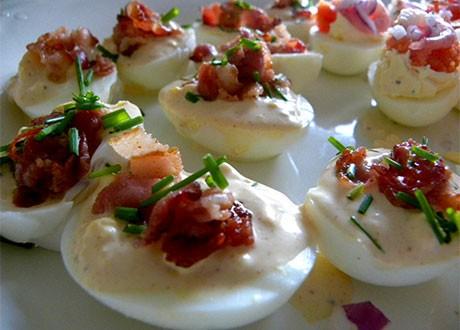 Ägghalvor med parikakräm och bacon på ett fat