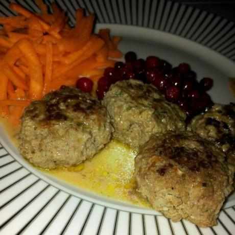 Köttbullar med lingon och morötter på en vitsvart randig tallrik