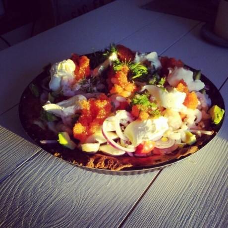 Kall paj med räkor och avocado på ett vitt bord