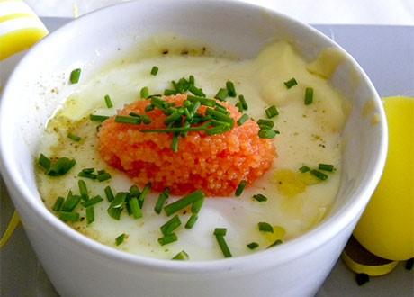 Pocherat ägg toppat med rom och gräslök i en vit skål