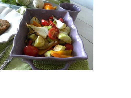 Ugnsrostade grönsaker, zucchini, paprika och lök i en lila ugnsform
