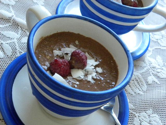 Chokladpudding toppad med hallon och kokoschips i en blå-vitrandig kopp