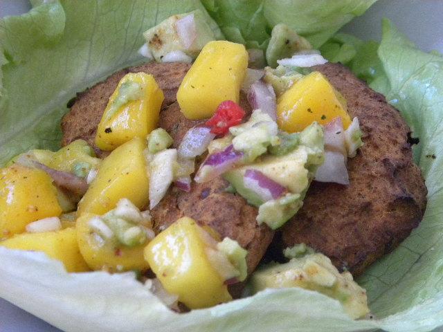 Vegetariska biffar gjorda av sötpotatis och kikärtor i ett salladsblad toppad med avocado och mangosalsa