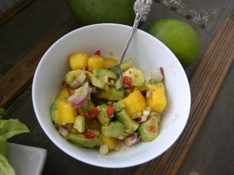 Mango och avocadosalsa i en vit skål på ett brunt bord