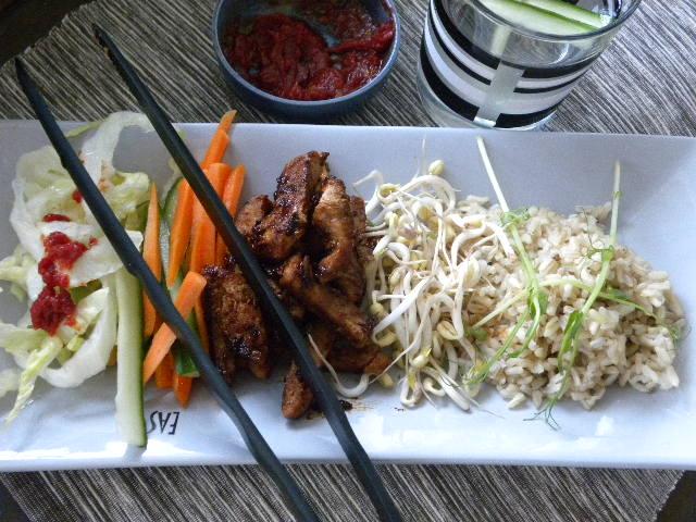 Ris, grönsaker och vegetariska sojabitar upplagda på ett grått fat, en blå skål med dressing och ett glas gurkvatten på en svartmelerad duk