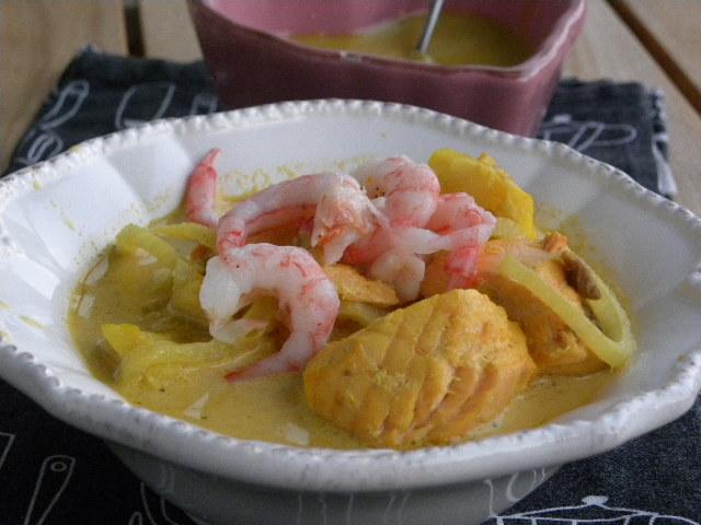 Fisksoppa toppade med räkor i en vit djup tallrik på en svart handuk
