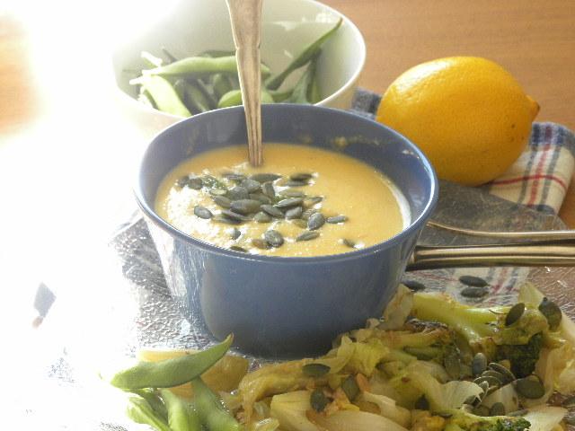 Rotfruktsoppa i en blå skål toppad med pumpafrö