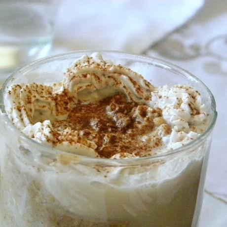 Coconut Latte Overnight Oat i ett glas toppad med kokosgrädde och kanel