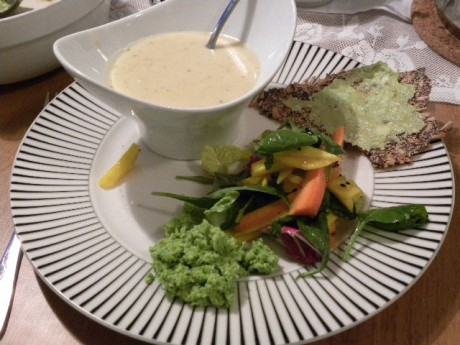 En flat tallrik med en vit soppskål med soppa, sallad, fröknäcke och ärthummus