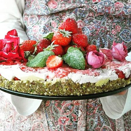 Någon klädd i förkläde håller en tårta dekorerad med jordgubbar och rosor