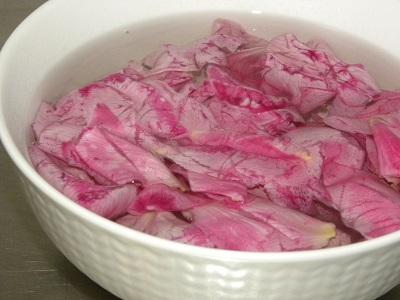 Rosenblad i vatten i en vit skål